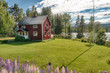 red rustic house on a green meadow - 60267540