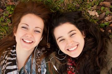 Happy teen girls sharing music