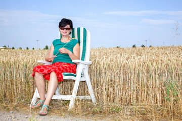 Woman sitting in the garden chair in front of the wheat field