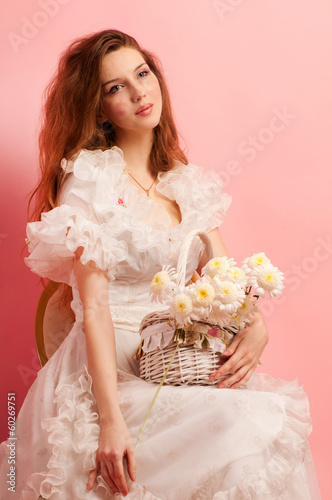 Studio portrait of a young beautiful lady in white dress