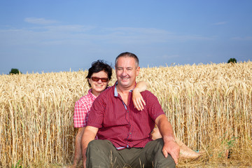 Woman and man sitting on the wheat field