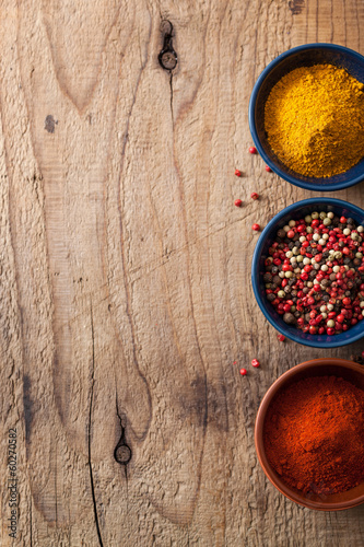 spices background: pink and black pepper, paprika powder, curry