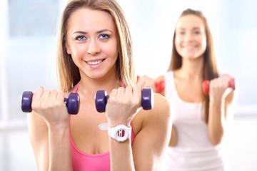 Trening z hantlami, dwie młode kobiety na siłowni