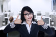 Smiling businesswoman with thumbs up