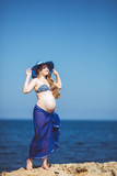 Young pregnant woman relaxing on a beautiful beach