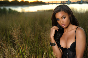Sexy African-american woman wearing lingerie at the grass field