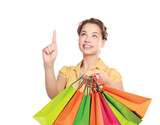 Young girl holding shopping bag and pointing up
