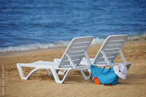 Sunchairs and Packed beach bag on empty sand beach