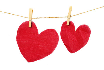 Red heart  hanging on clothesline on white background.
