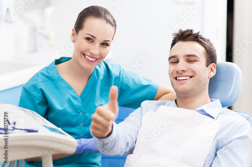 Man giving thumbs up at dentist office - 60275739