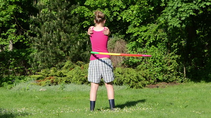 woman turn spin hula hoop ring on waist in morning garden