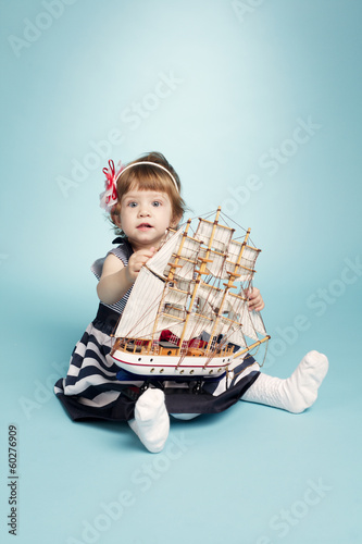 cute girl in a sea clothes with model ship