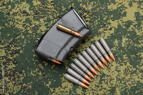 Filled magazine and eleven cartridges on digital camouflage