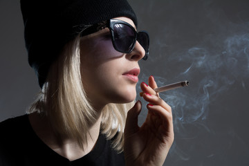 Portrait of a young girl wearing sunglasses smoking a cigarette