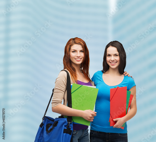two smiling students with bag and folders