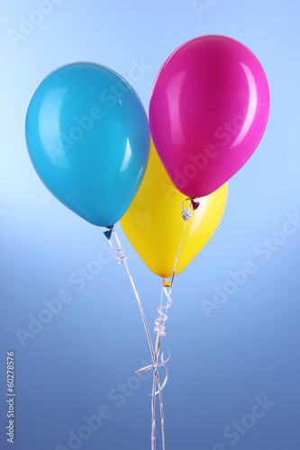 Three colorful balloons on blue background