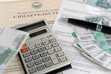 Калькулятор, деньги, ручка и требование на фоне свидетельства