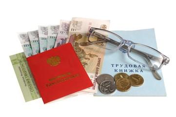 Пенсионные документы с деньгами и очками на белом фоне