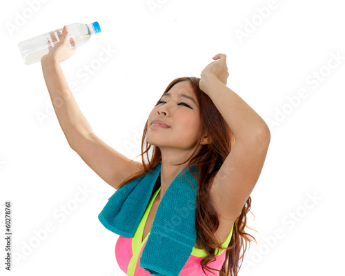 Attractive Asian woman with water bottle and towel after exercis
