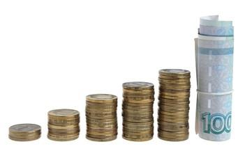 Пять стопок монет и сверток купюр на белом фоне