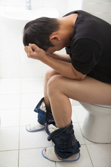 adult man with frustrated expression sitting toilet seat