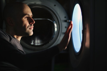 man looking into a washing machine