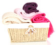 Warm knitted scarves in basket isolated on white