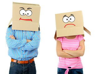 Couple with cardboard boxes on their heads isolated on white