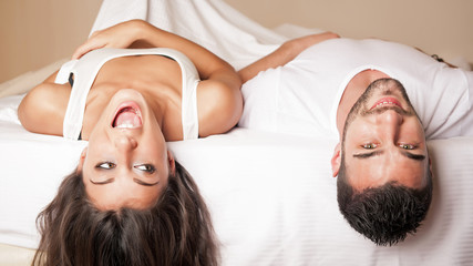 Happy young couple portrait having fun upside down in hotel room