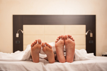 Couple relaxing in hotel room under sheets. Close up on feet.