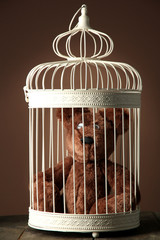 Toy bear in decorative cage on wooden table, on brown