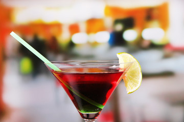 Glass of tasty cocktail on bright background