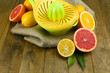 Citrus press and fruits on wooden background
