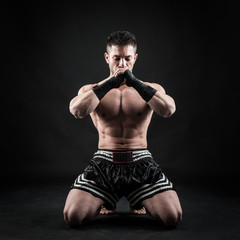Sportsman kick boxer meditation portrait against black backgroun