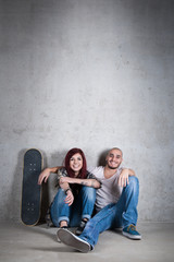 Happy couple portrait sit on the ground with skateboard against