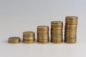 Пять стопок монет на сером фоне