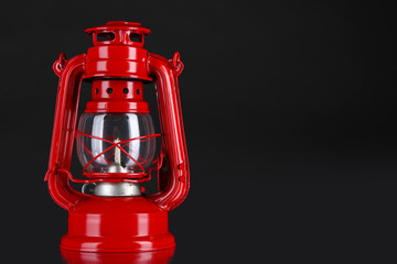 Red kerosene lamp on black background