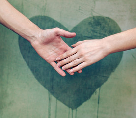 Man touching woman's hand with a heart painted wall in backgroun