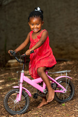 Littel african girl on bicycle.