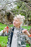 Woman cuts a branch tree in the garden
