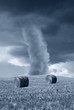 tornado in the country with round bales