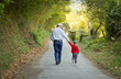 Grandfather and grandchild walking in nature path - 60287307