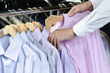 Man choosing shirt from the raw in the shop.