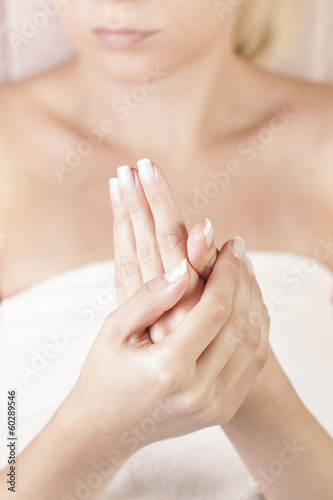 female applying cream on her hands