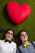 Nerdy couple in love lying down on grass