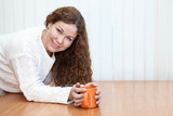 Woman with orange mug in hands looking at camera copyspace