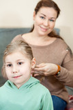 Mother raiding hair of her child sitting in domestic room poster