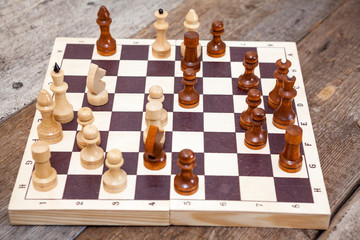 Chess wooden figures in game on timber floor