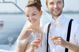 Happy bride and groom drinking champagne