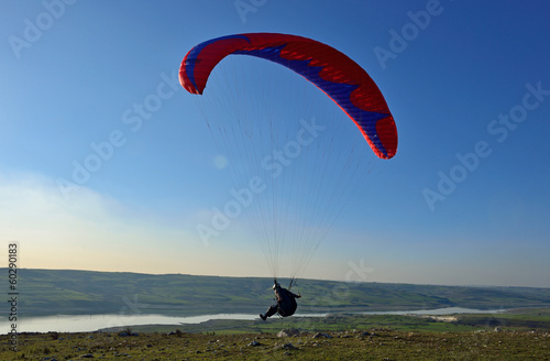 Fototapeta Paraglider taking off from a mountain